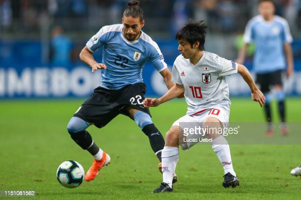 Martín Cáceres of Uruguay battles for the ball against Shoya Nakajima of Japan during the Copa America Brazil 2019 group C match between Uruguay and...