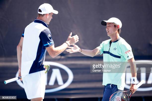 Marton Fucsovics of Hungary and Yoshihito Nishioka of Japan talk tactics in their first round men's doubles match against Bob Bryan of the United...