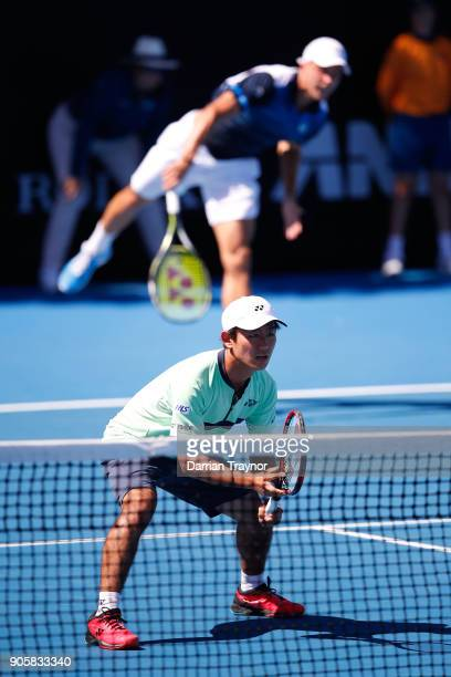 Marton Fucsovics of Hungary serves in his first round men's doubles match with Yoshihito Nishioka of Japan against Bob Bryan of the United States and...