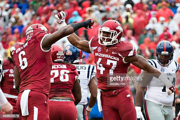 Martrell Spaight and JaMichael Winston of the Arkansas Razorbacks celebrate after a play against the Ole Miss Rebels at Razorback Stadium on November...