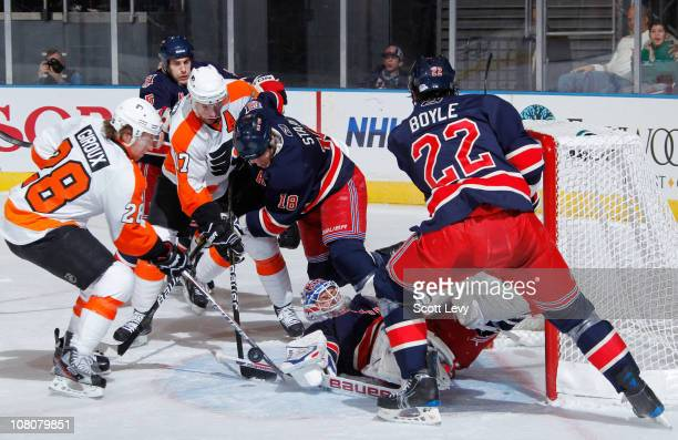 Marty Biron of the New York Rangers protects the net in the first period against Claude Giroux and Jeff Carter of the Philadelphia Flyers on January...