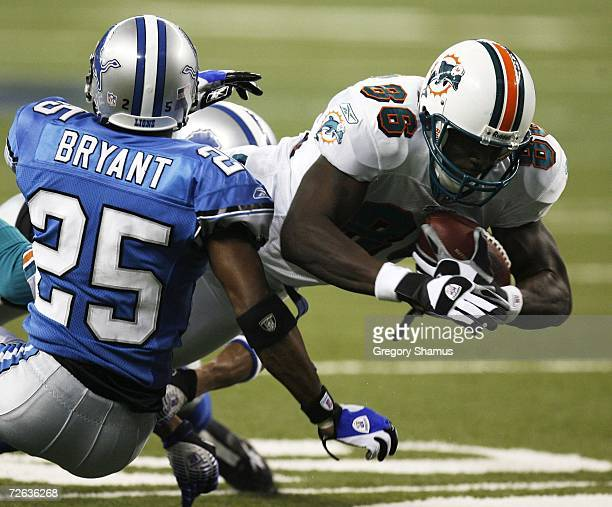 Marty Booker of the Miami Dolphins dives past the tackle of Fernando Bryant of the Detroit Lions during second quarter action on November 23 2006 at...