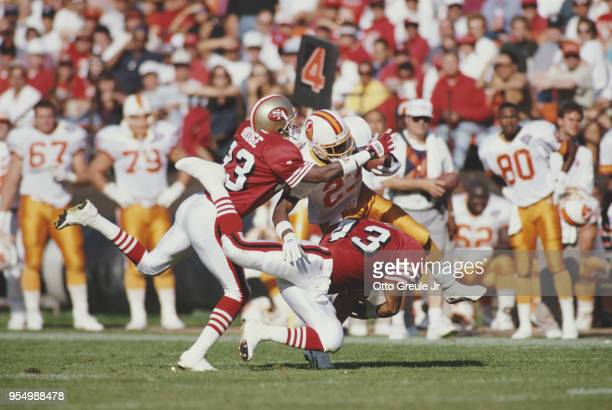 Marty Carter Strong Safety for the Tampa Bay Buccaneers is tackled by Marc Logan and Dedrick Dodge of the San Francisco 49ers during their National...