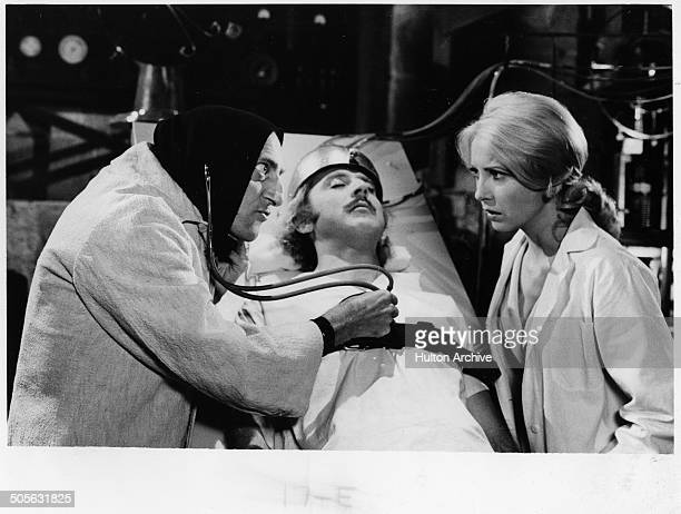 Marty Feldman listens to Gene Wilders' heart as Teri Garr looks on in a scene from the movie Young Frankenstein circa 1974
