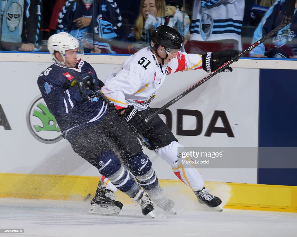 Marty Sertich #26 of Hamburg Freezers slides into Kristian Näkyvä #51 of Lulea Hockey during the Champions Hockey League group stage game between Hamburg Freezers and Lulea HF on August 22, 2014 in Hamburg, Germany.