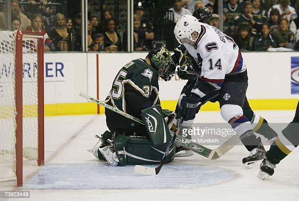 Marty Turco of the Dallas Stars makes a save on Alexandre Burrows of the Vancouver Canucks during game three of the 2007 NHL Western Conference...