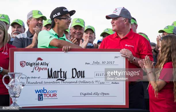 Marty Zecheng Dou receives his winners check from Rick Amos of Digital Ally after winning the Digital Ally Open of the WEBCOM Tour at Nicklaus Golf...