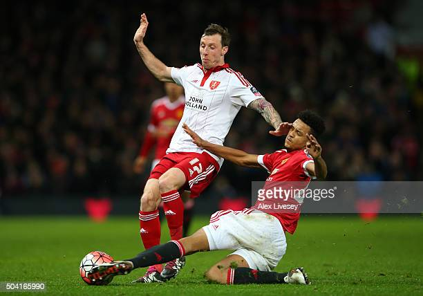 Martyn Woolford of Sheffield United is tackled by Cameron Borthwick-Jackson of Manchester United during the Emirates FA Cup Third Round match between...
