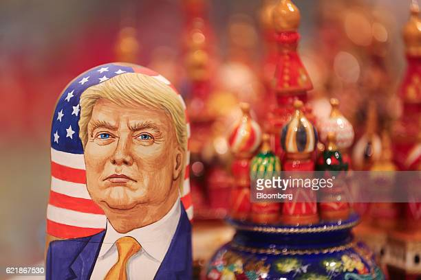 A martyoshka doll showing Donald Trump US president elect sits beside painted wooden models of St Basil's cathedral in a souvenir store in Moscow...