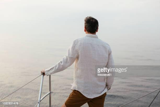 marure man on catamaran, looking ta view - garde corps photos et images de collection