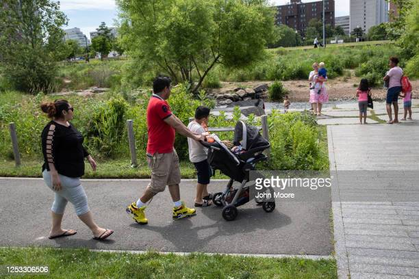 Marvin and Zully walk with their sons Junior and Neysel, 10 weeks, at a park on June 25, 2020 in Stamford, Connecticut. Marvin, Zully and Junior...