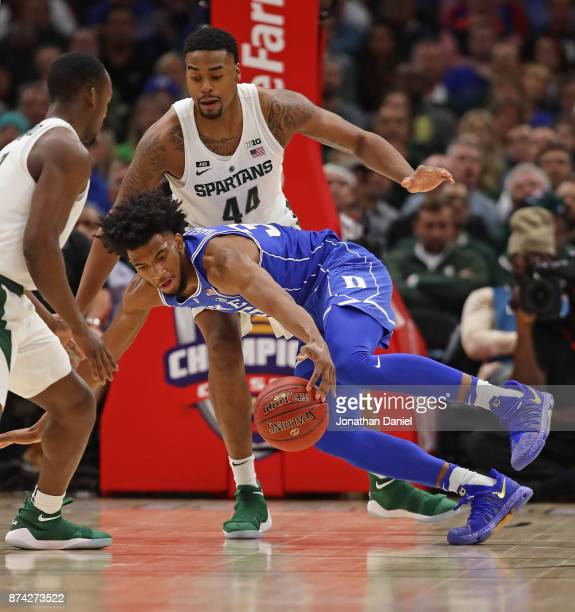 Marvin Bagley III of the Duke Blue Devils tries to control the ball under pressure from Nick Ward of the Michigan State Spartans during the State...