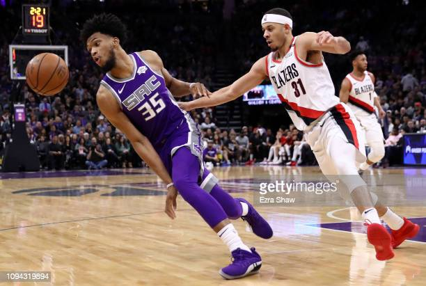 Marvin Bagley III of the Sacramento Kings and Seth Curry of the Portland Trail Blazers go for a loose ball at Golden 1 Center on January 14 2019 in...