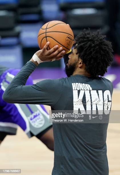 "Marvin Bagley III of the Sacramento Kings warming up wears a Nike basketball shooting shirt that displays on the back ""HONOR KING"" honoring Dr...."