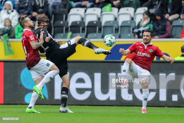 Marvin Bakalorz of Hannover Julian Korb of Hannover and Christoph Kramer of Moenchengladbach battle for the ball during the Bundesliga match between...