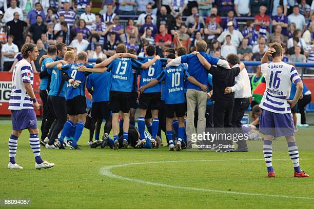 Marvin Braun and Fiete Sykora of Osnabrueck look dejected while players of Paderborn celebrate the ascension to the Second Bundesliga after the...