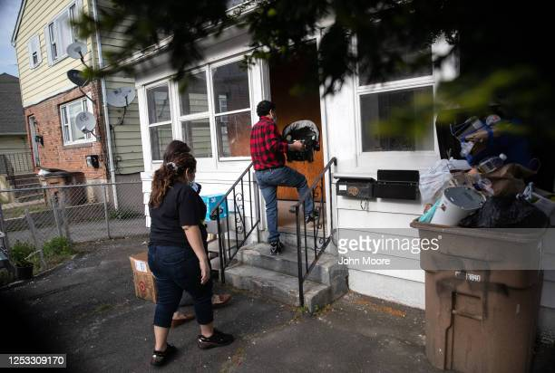 Marvin carries his son Neysel 6 weeks into their home on May 14 2020 in Stamford Connecticut The Guatemalan immigrant family fell sick to Covid19 in...