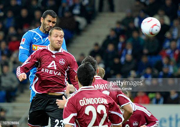 Marvin Compper of Hoffenheim scores the opening goal with a headkick against Julian Schieber of Nuernberg during the Bundesliga match between 1899...