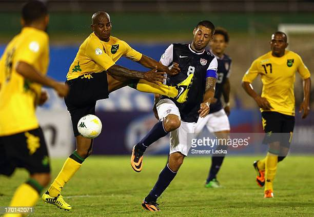 Marvin Elliot of Jamaica battles for a ball with Clint Dempsey of the USA during the FIFA 2014 World Cup Qualifier at National Stadium on June 7,...