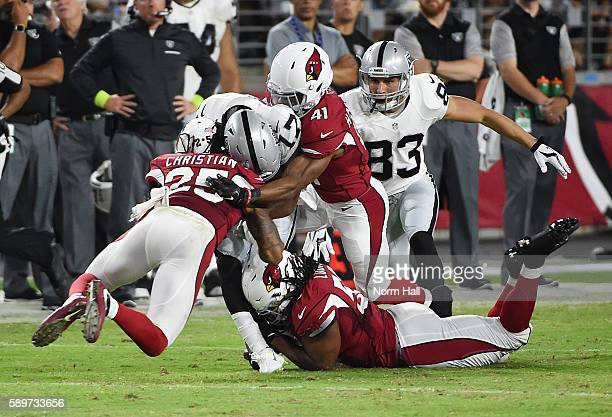 Marvin Hall of the Oakland Raiders is tackled by Marqui Christian, Trevon Hartfield and Lamar Louis of the Arizona Cardinals at University of Phoenix...
