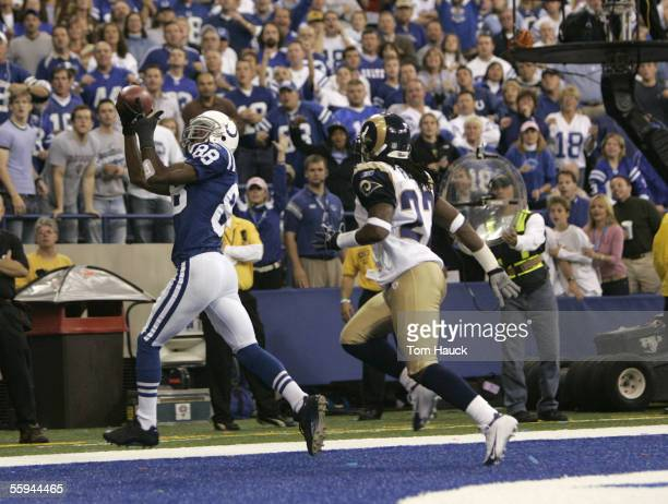 Marvin Harrison catches a touchdown pass from quarterback Peyton Manning of the Indianapolis Colts against Travis Fisher of the St Louis Rams on...