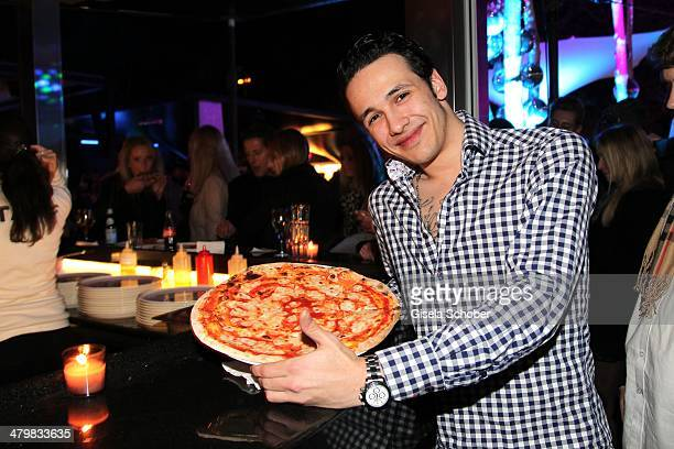Marvin Herzsprung with a H'ugo's Pizza attends the 30 year anniversary celebration of the club P1 on March 20, 2014 in Munich, Germany.