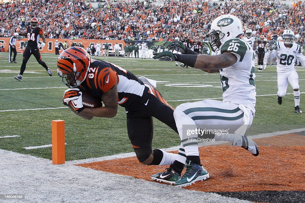 Marvin Jones #82 of the Cincinnati Bengals hauls in a touchdown pass in front of Dawan Landry #26 of the New York Jets during their game at Paul Brown Stadium on October 27, 2013 in Cincinnati, Ohio. The Bengals defeated the Jets 49-9.