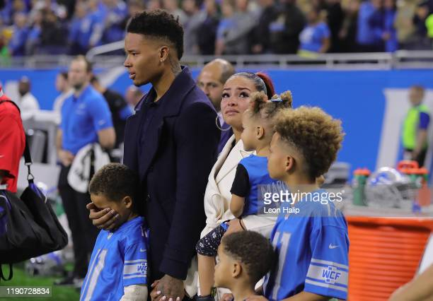Marvin Jones of the Detroit Lions and his family stand on the sidelines during a moment of silence for the passing of their young son, prior to the...
