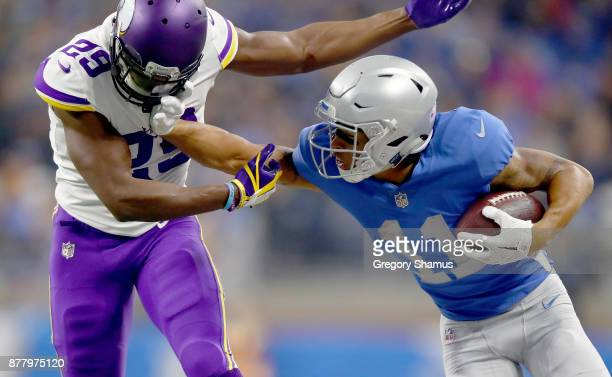 Marvin Jones of the Detroit Lions fights off defender Xavier Rhodes of the Minnesota Vikings after catching a pass during the first half at Ford...