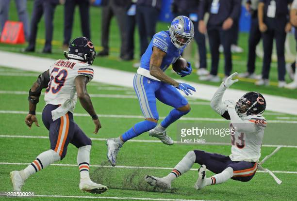 Marvin Jones of the Detroit Lions makes the catch and a short run for a first down as Jaylon Johnson of the Chicago Bears attempts to make the tackle...