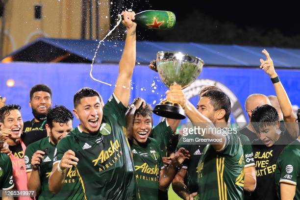 Marvin Loria and Bill Tuiloma of Portland Timbers celebrate with the champions trophy after defeating Orlando City 2-1 in the final match of MLS Is...