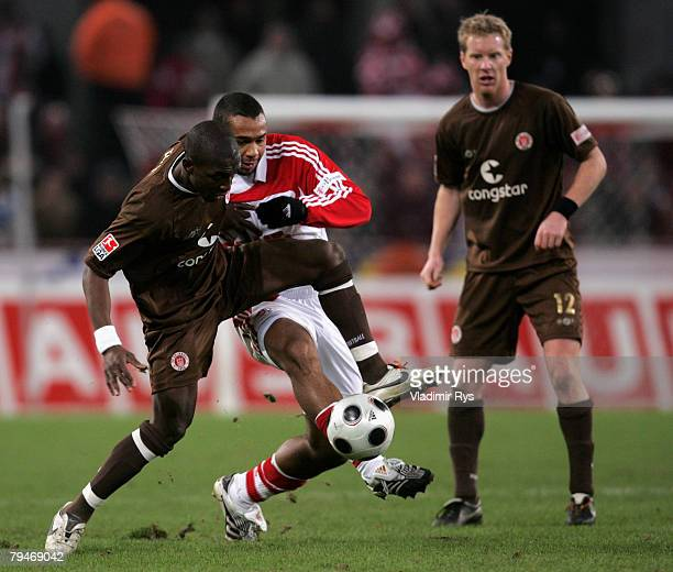 Marvin Matip of Cologne and Charles Takyi of Pauli battle for the ball as Pauli player Timo Schultz looks on during the second Bundesliga match...