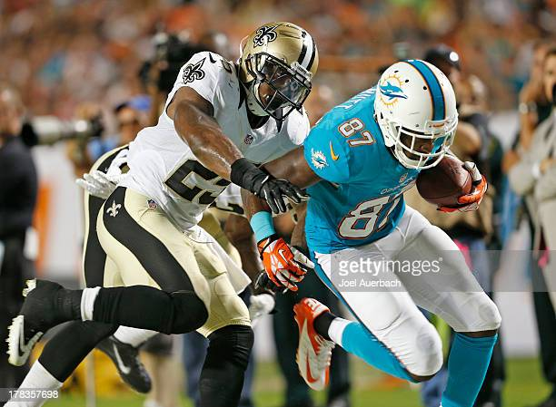 Marvin McNutt of the Miami Dolphins is knocked out of bounds by Rafael Bush of the New Orleans Saints as he runs with the ball during a preseason...
