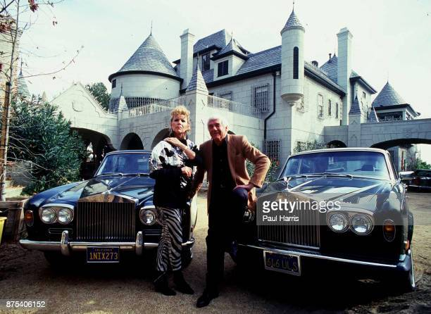 Marvin Mitchelson and his wife Marcella pose in front of two Rolls Royce cars and their palatial home on January 1 1989 in West Hollywood California