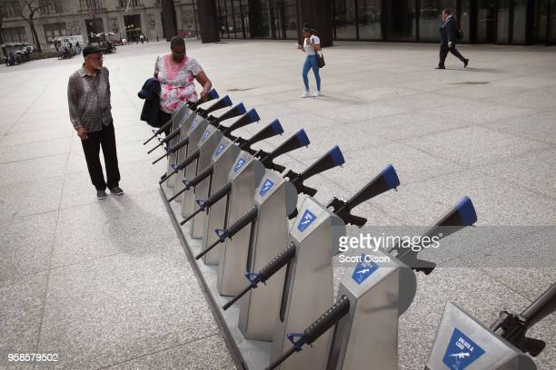 Marvin Mosley and Jonikka Raines look over the Chicago Gun Share Program art installation in the Daley Center plaza on May 14 2018 in Chicago...