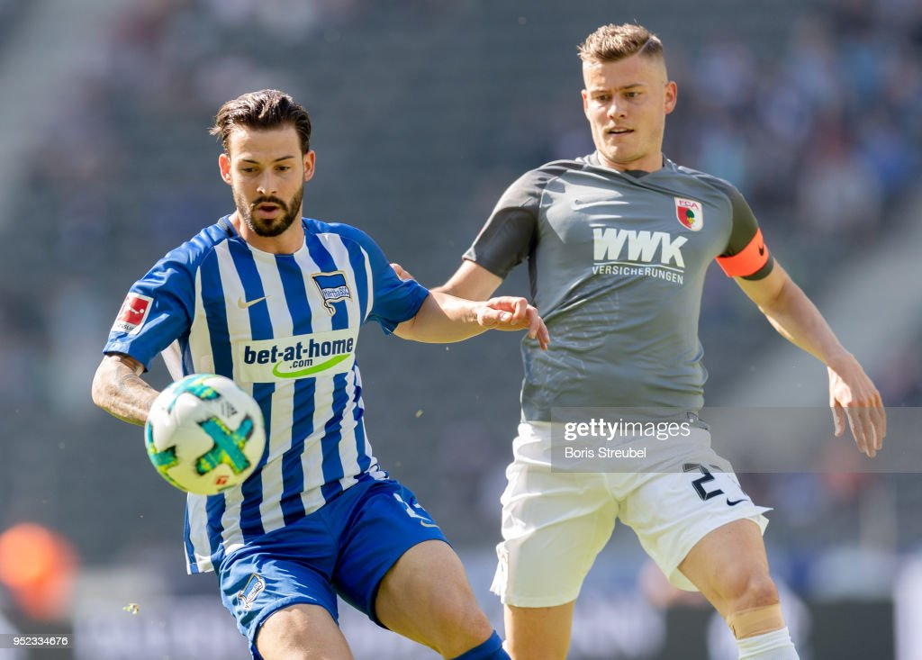 Marvin Plattenhardt of Hertha BSC is challenged by Alfred Finnbogason of FC Augsburg during the Bundesliga match between Hertha BSC and FC Augsburg at Olympiastadion on April 28, 2018 in Berlin, Germany.