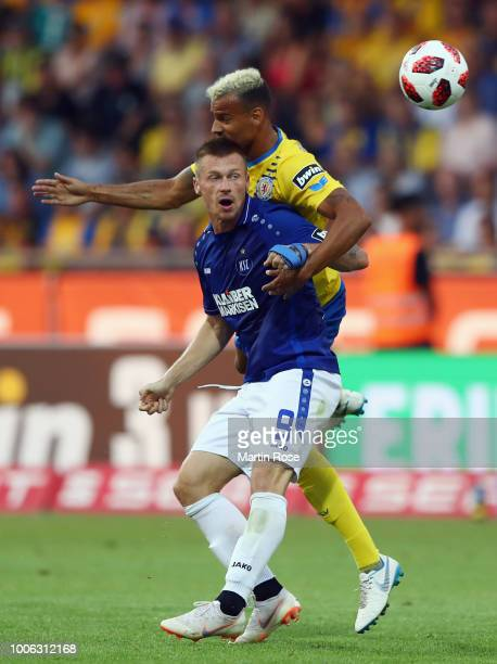 Marvin Pourie of Karlsruhe is challenged by Steffen Nkansah of Braunschweig during the 3 Liga match between Eintracht Braunschweig and Karlsruher SC...