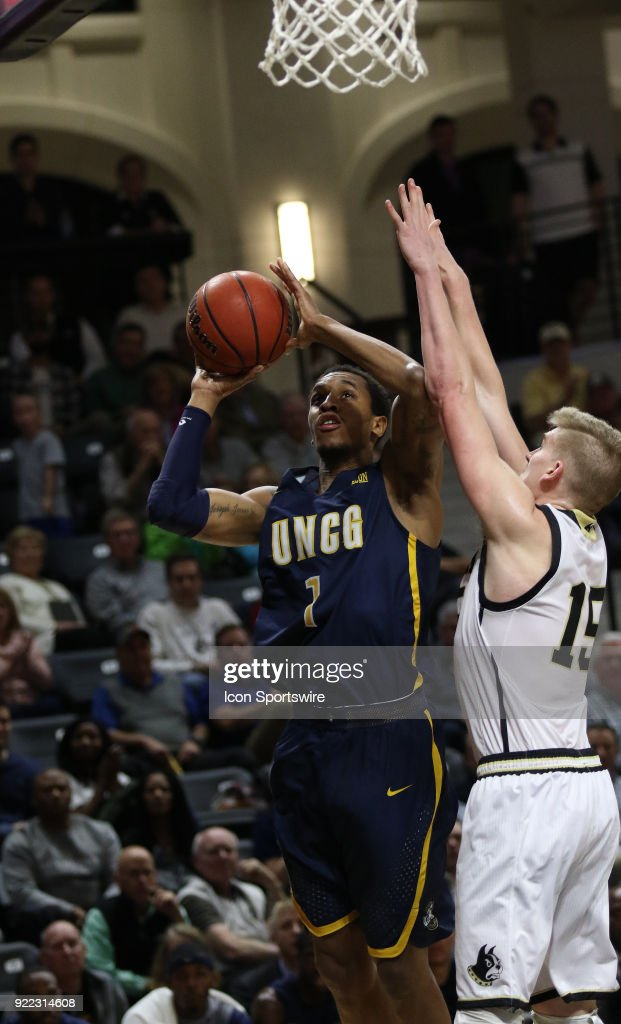 Marvin Smith (1) UNC Greensboro looks to put the ball up past the outstretched arms of Trevor Stumpe (15) guard Wofford College Terriers, during action against Wofford at Jerry Richard indoor stadium in Spartanburg,SC on Tuesday February 20, 2018.