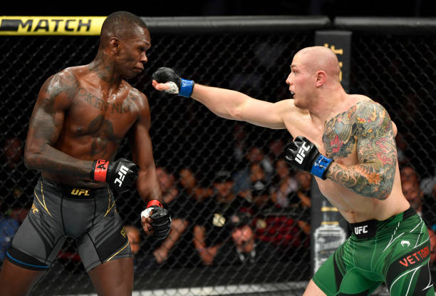 Marvin Vettori of Italy punches Israel Adesanya of Nigeria in their UFC middleweight championship fight during the UFC 263 event at Gila River Arena...