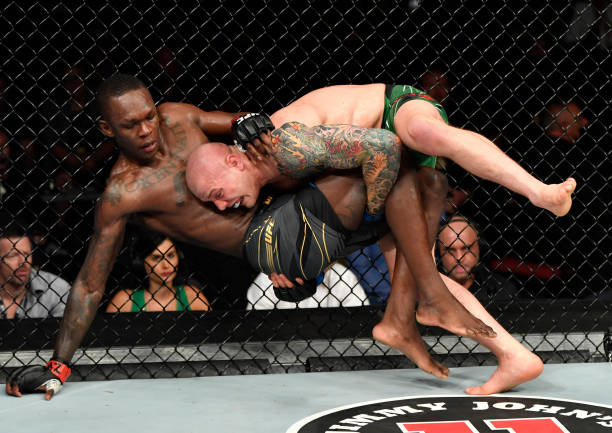 Marvin Vettori of Italy takes down Israel Adesanya of Nigeria in their UFC middleweight championship fight during the UFC 263 event at Gila River...