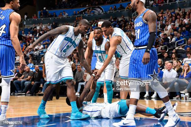 Marvin Williams and Miles Bridges of the Charlotte Hornets help up a teammate during the game against the Orlando Magic on February 14 2019 at Amway...