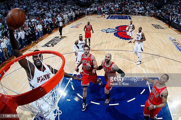 Marvin Williams of the Atlanta Hawks dunks against Derrick Rose, Joakim Noah and Carlos Boozer of the Chicago Bulls in Game Three of the Eastern...