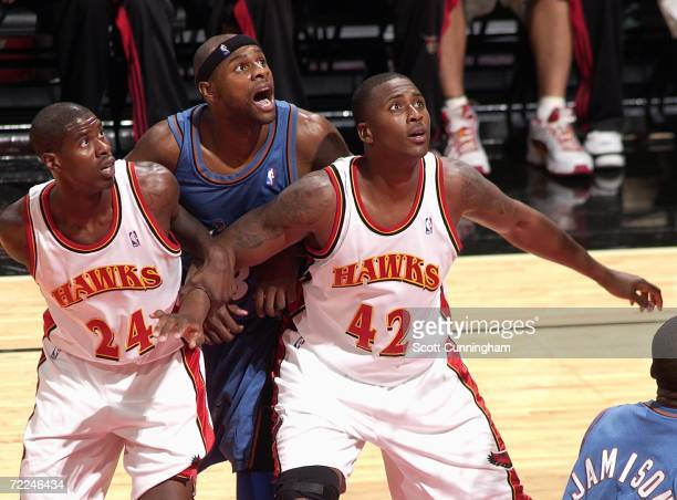 Marvin Williams of the Atlanta Hawks grabs the arm of Lorenzen Wright to block out Brendan Haywood of the Washington Wizards at Philips Arena on...