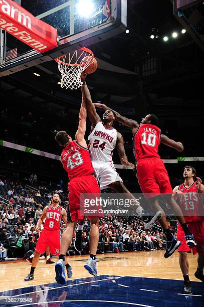 Marvin Williams of the Atlanta Hawks shoots against Kris Humphries and Damion James of the New Jersey Nets on December 30 2011 at Philips Arena in...