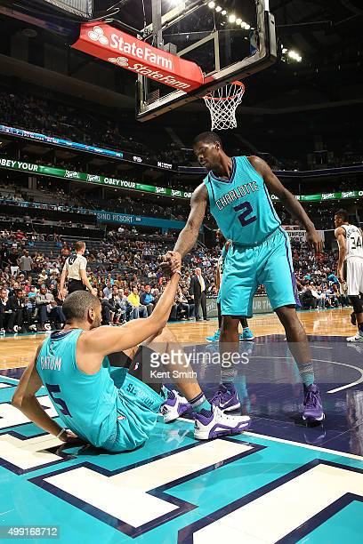 Marvin Williams of the Charlotte Hornets helps his teammate Nicolas Batum of the Charlotte Hornets up during the game against the Milwaukee Bucks on...