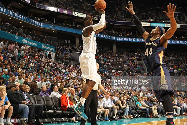 Marvin Williams of the Charlotte Hornets shoots against Dante Cunningham of the New Orleans Pelicans during the game at the Time Warner Cable Arena...