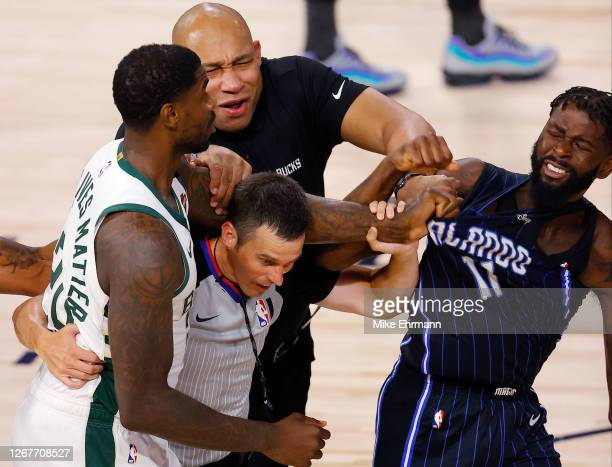 Marvin Williams of the Milwaukee Bucks grabs the jersey of James Ennis III of the Orlando Magic as referee Kevin Scott and Bucks assistant coach...