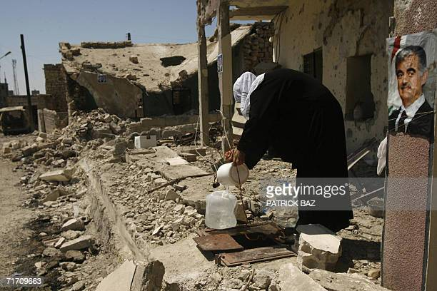 A Lebanese woman fills water near a poster plastered on a wall of late assassinated Lebanese premier Rafic Hariri on a house in the Sunni...