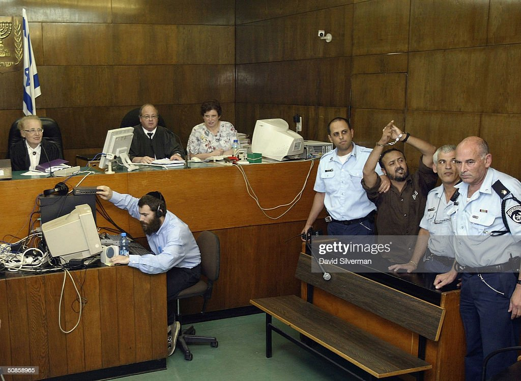 Marwan Barghouti, head of the Palestinian Fatah Tanzim and al-Aksa Martyrs Brigades, gestures as he is escorted by Israeli police into the District Court May 20, 2004 in Tel Aviv for his judgement hearing. Barghouti was convicted of five counts of murder.