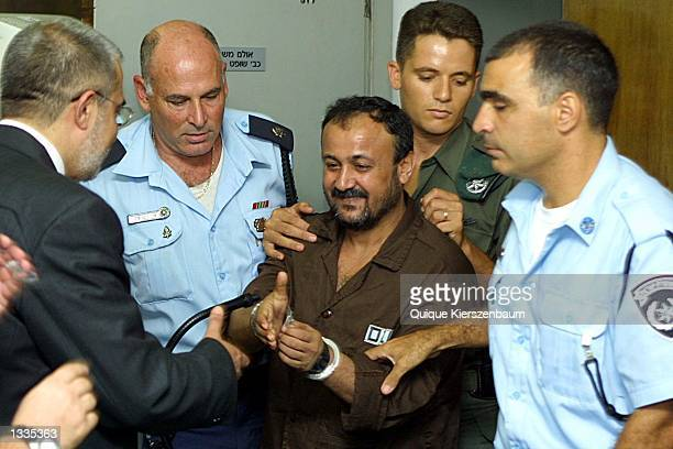 Marwan Barghouti the West bank chief of Yasser Arafats Fatah movement is greeted by his lawyer Jawad Boulos in the courtroom on the opening day of...